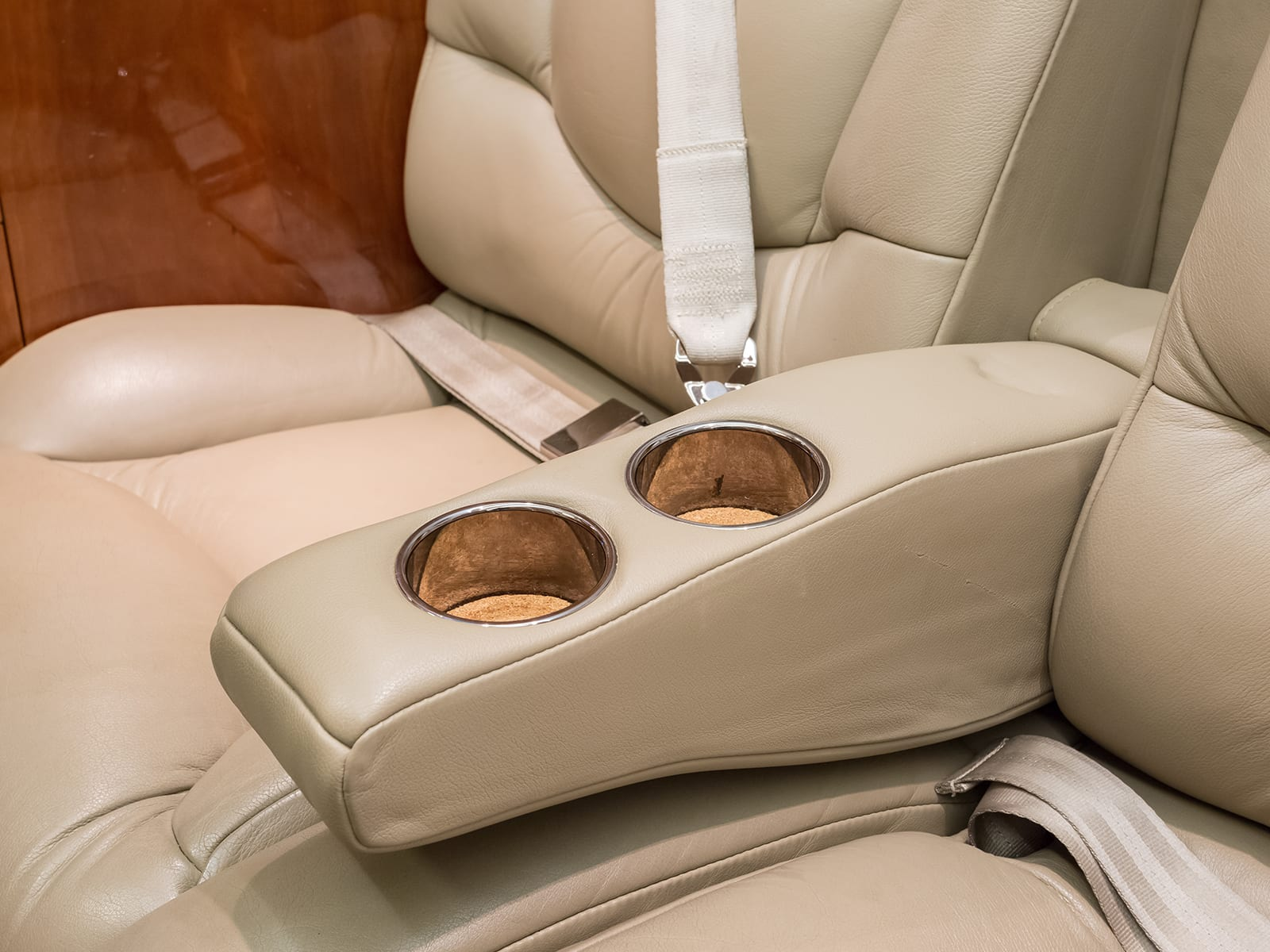 a cup holder and armrest in a Priority Jet aircraft