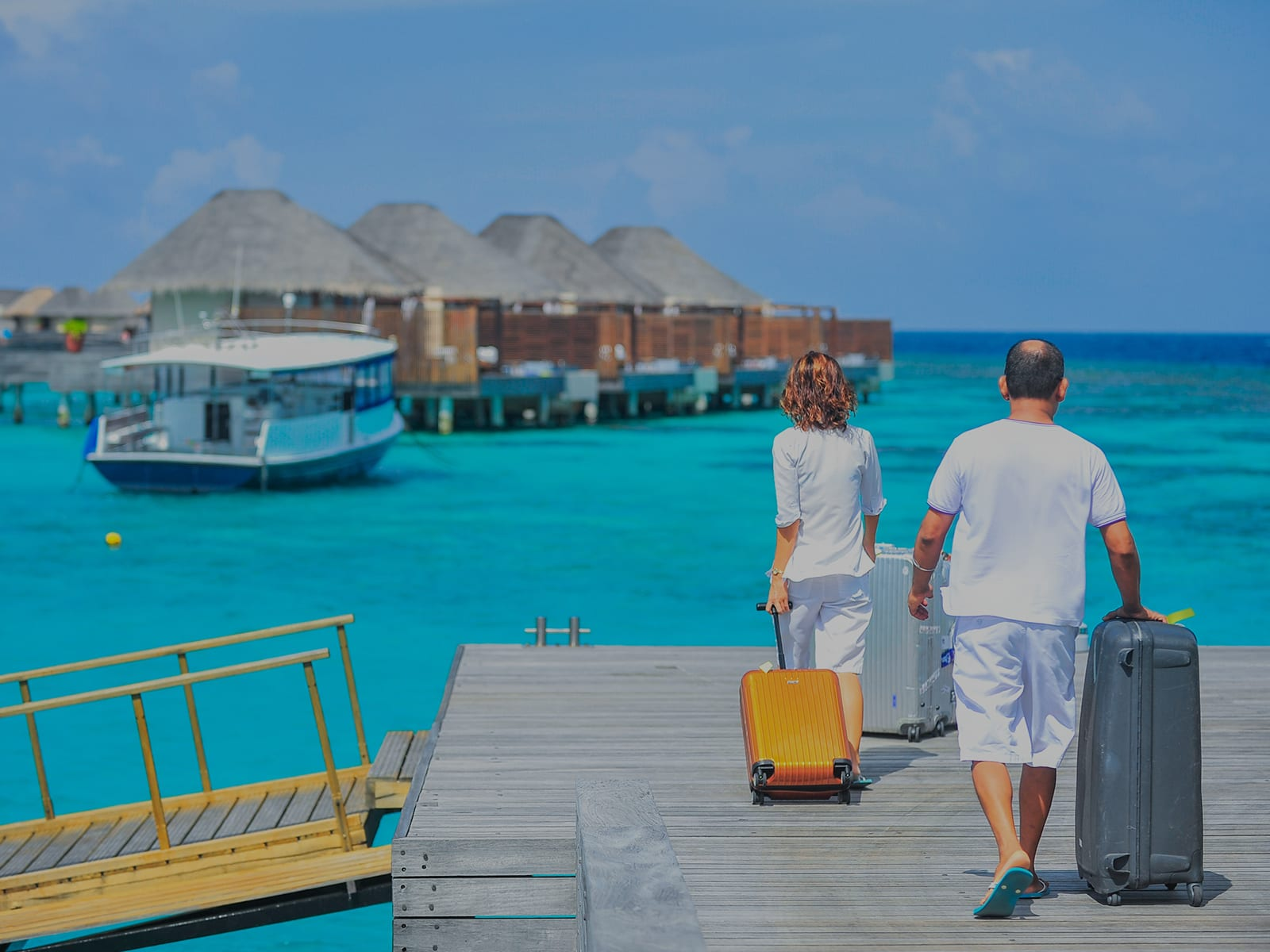 Two vacationers walking on a pier with luggage during travel