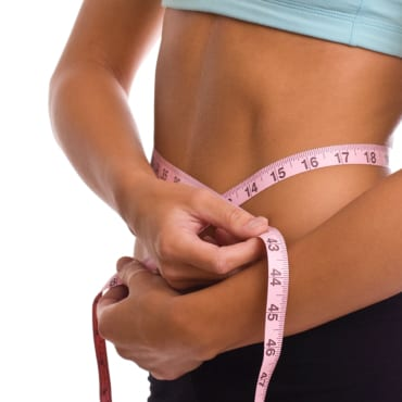 A woman measuring weight loss from Discover Chiropractic